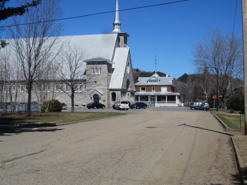 Au bout de la rue Morel, vous allez apercevoir le presbytère et l'église; continuez d'avancer.
